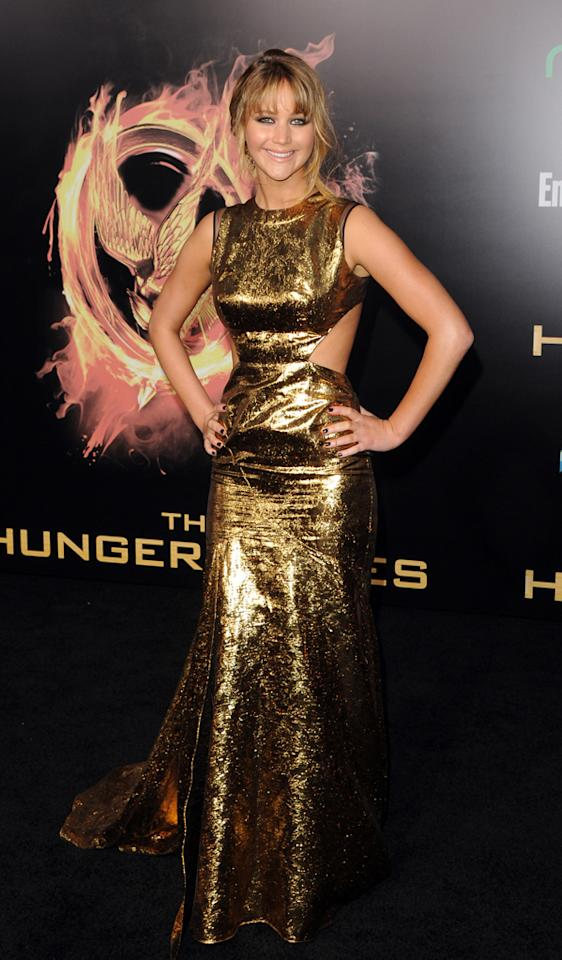 "Jennifer Lawrence rocked a golden look at the world premiere of ""The Hunger Games"" in Los Angeles. Her Prabal Gurung dress included cutout sides and a futuristic metallic sheen, and she paired the gown with Jimmy Choo heels and black diamond earrings. Fans went wild for the star and her style, but Lawrence saved her enthusiasm for something simple -- an opportunity to ""sleep in a bed soon."""
