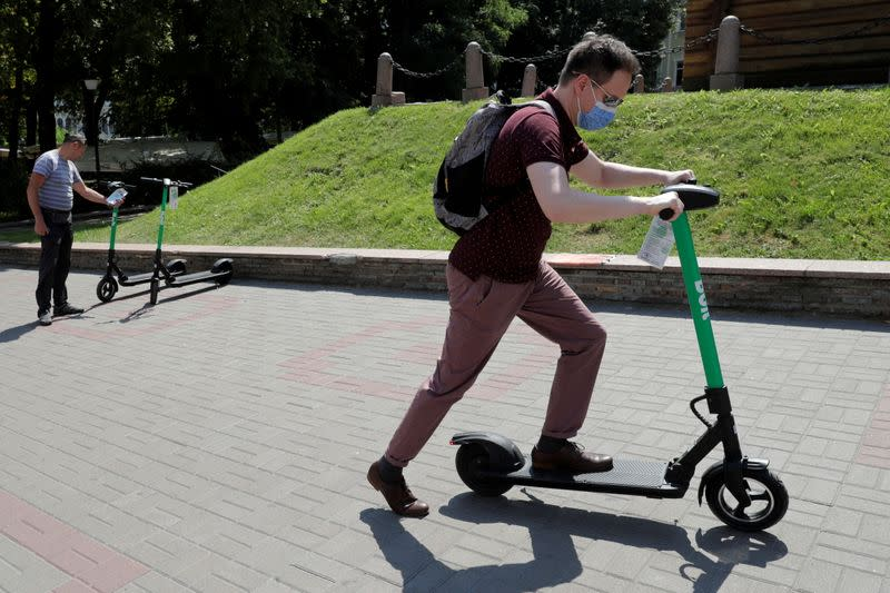 FILE PHOTO: A man uses an e-scooter from provider Bolt in central Kyiv