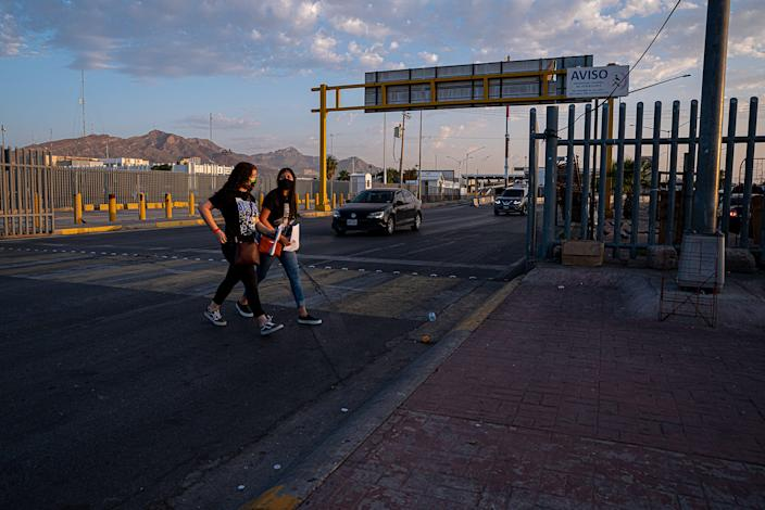 Two young women with masks and backpacks walk towards the Bridge of the Americas at sunrise in El Paso on Sept. 23, 2020.