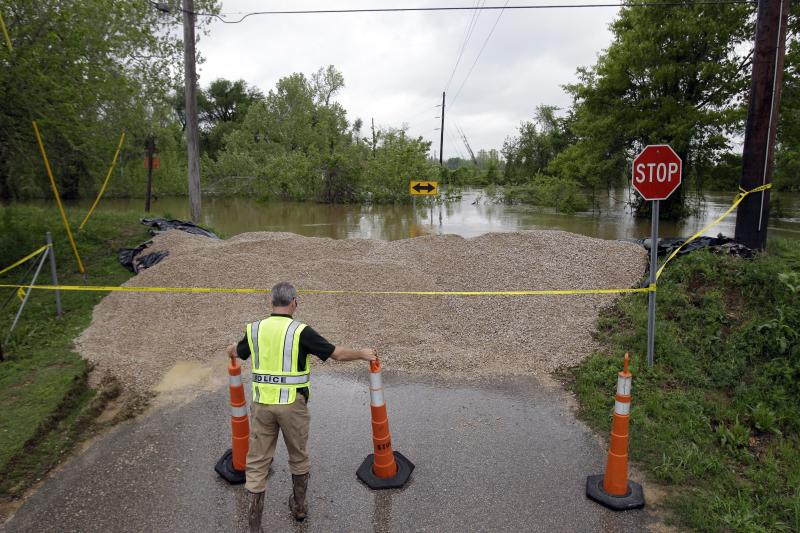 Detective Corey Mitchell with the Poplar Bluff Police Department adjusts traffic cones near a temporary levee holding back water from the Black River Tuesday, April 26, 2011, in Poplar Bluff, Mo. Powerful storms that swept through the nation's midsection have pushed river levels to dangerous heights and are threatening to flood several towns in Missouri and officials now report another levee area protecting Poplar Bluff from the Black River has breached. (AP Photo/Jeff Roberson)