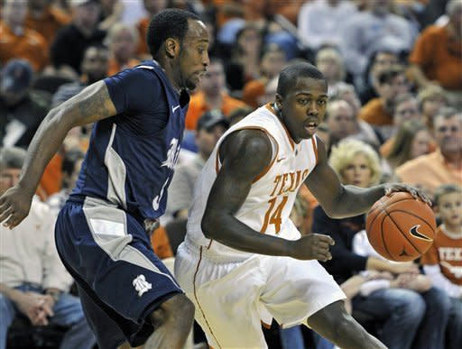 Texas guard J'Covan Brown, right, drives around Rice guard Tamir Jackson during the first half of an NCAA college basketball game Saturday, Dec. 31, 2011, in Austin, Texas. (AP Photo/Michael Thomas)