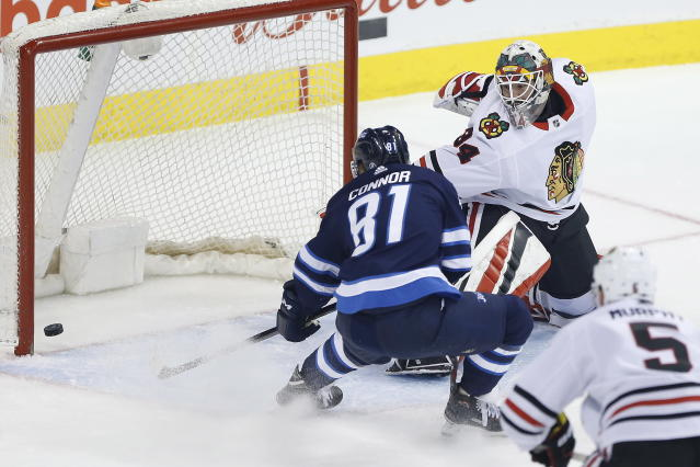 Winnipeg Jets left wing Kyle Connor (81) scores on Chicago Blackhawks goaltender J-F Berube (34) as Connor Murphy (5) defends during the first period of an NHL hockey game Thursday, March 15, 2018, in Winnipeg, Manitoba. (John Woods/The Canadian Press via AP)