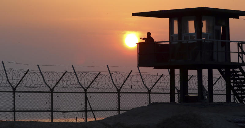 A South Korean soldier guards with his gun at a guard post at sunrise on Baengnyeong Island, South Korea, near the West Sea border with North Korea Wednesday, April 2, 2014. South Korea suspects that an unmanned drone that crashed on a frontline South Korean island was flown by rival North Korea. The drone crashed on Baengnyeong island Monday when the two Koreas fired hundreds of artillery shells into each other's waters in a flare-up of animosity over a long-disputed sea boundary between the countries. (AP Photo/Yonhap, Hong Hae-in) KOREA OUT