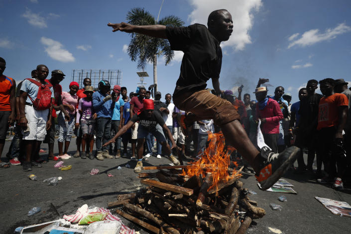 A man jumps over a fire during a voodoo ceremony to grant protection to the people, as protesters calling for the resignation of President Jovenel Moise gathered at a bridge in the Delmar area of Port-au-Prince, Haiti, Thursday, Oct. 17, 2019. Haiti's embattled president was forced on Thursday to hold a private ceremony amid heavy security for what is usually a public celebration of one of the country's founding fathers, revolution leader Jean-Jacques Dessalines. (AP Photo/Rebecca Blackwell)