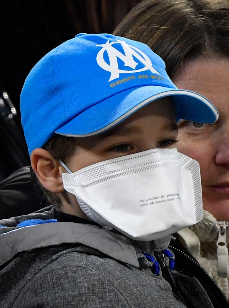 A young Marseille's supporter wears a protective face mask as a protection against COVID-19 caused by the novel coronoavirus, prior to the French L1 football match between Olympique de Marseille (OM) and Amiens (ASC) at the Velodrome Stadium in Marseille, southern France, on March 6, 2020. (Photo by GERARD JULIEN / AFP) (Photo by GERARD JULIEN/AFP via Getty Images)