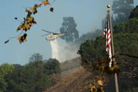 <p>A helicopter attempts to fan the flames by spraying water (Picture: Yahoo Photo Staff) </p>