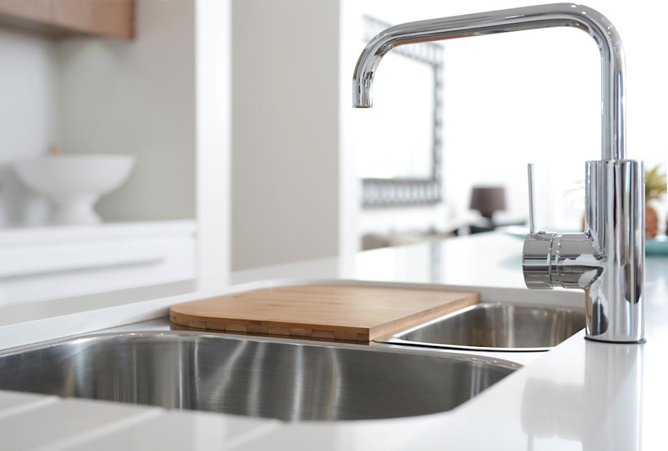 Modern stainless-steel faucet and sink on kitchen,with chopping board on top of sink