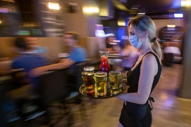 Restaurant owners and managers around Ottawa say it's busier than ever as COVID-19 restrictions continue to ease in Ontario — but finding enough workers to serve those all those hungry and thirsty diners is proving a big problem. (Lars Hagberg/The Canadian Press - image credit)