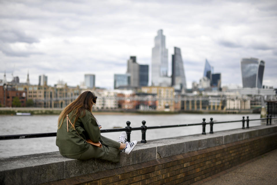 A woman sits on the edge of the south bank of the river Thames, in London, Monday, Aug. 31, 2020. Today is the last day of the 'Eat out to help out' scheme, the UK Government's initiative to support restaurants, cafés, bars and pubs. (AP Photo/Alberto Pezzali)