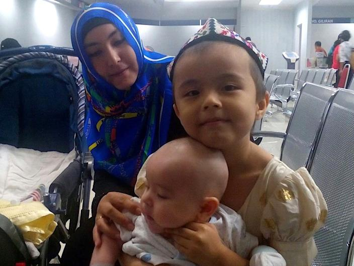 Abdurehim's wife and children at the Birth Registration Office in Kuala Lumpur, Malaysia, applying for his son Hikmet's birth certificate, in August 2015.