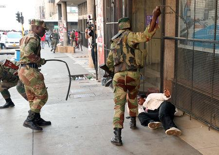FILE PHOTO: Soldiers beat a supporter of the opposition Movement for Democratic Change party of Nelson Chamisa outside the party's headquarters as they await the results of the general elections in Harare, Zimbabwe, August 1, 2018. REUTERS/Mike Hutchings/File Photo