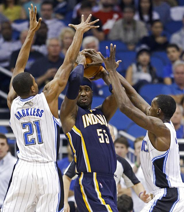 Indiana Pacers' Roy Hibbert (55) looks to pass the ball as he is caught between Orlando Magic's Maurice Harkless (21) and Dewayne Dedmon, right, during the first half of an NBA basketball game in Orlando, Fla., Wednesday, April 16, 2014. (AP Photo/John Raoux)