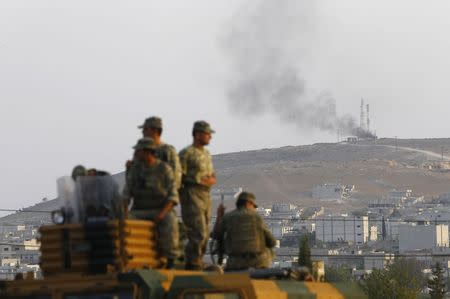 Turkish soldiers are seen on top of an armoured vehicle, with the Syrian town of Kobani in the background, near the Mursitpinar border crossing
