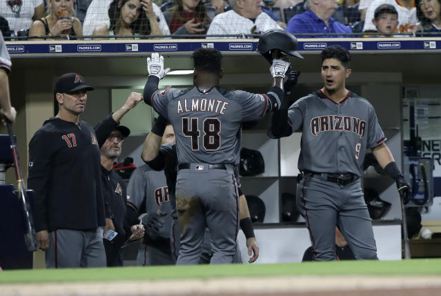 Arizona Diamondbacks' Abraham Almonte (48) gets congratulations from Josh Rojas, right, and other teammates after scoring on a fielder's choice during the sixth inning of a baseball game against the San Diego Padres in San Diego, Saturday, Sept. 21, 2019. (AP Photo/Alex Gallardo)
