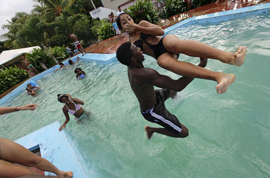 <p>Carmen Gonzalez (R) is carried into a swimming pool by a friend during her quinceanera.</p>