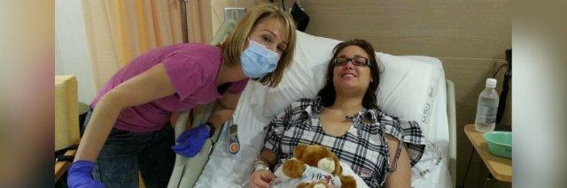 The author laying in a hospital bed with her mom standing next to her. Her mom is wearing a face mask.