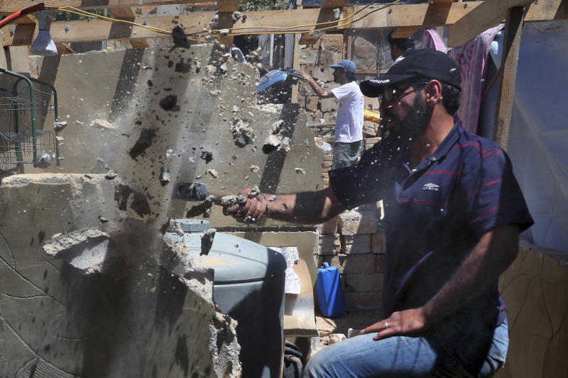 In this Sunday, June 16, 2019 photo, a Syrian refugee demolishes a concrete wall built inside his tent at a refugee camp in the eastern Lebanese border town of Arsal, Lebanon. Authorities in Lebanon are waging their most aggressive campaign yet against Syrian refugees, making heated calls for them to go back to their country and taking action to ensure they can't put down roots. They are shutting down shops where Syrians work without permits and ordering the demolition of anything in their squalid camps that could be a permanent home. (AP Photo/Bilal Hussein)