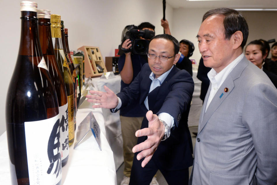 Then Chief Cabinet Secretary Yoshihide Suga, right, receives a briefing on hometown tax donation in Miyakonojo city, Miyazaki prefecture, southern Japan on June 15, 2016. Japan's Parliament elected Suga as prime minister Wednesday, Sept. 16, 2020, replacing long-serving leader Shinzo Abe with his right-hand man. Suga has stressed his background as a farmer's son and a self-made politician in promising to serve the interests of ordinary people and rural communities. (Kyodo News via AP)