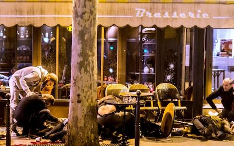 People lie on the pavement at the terrasse of the Cafe Bonne Biere in Paris, following a series of coordinated attacks in and around Paris on November 13, 2015 - Credit: ANTHONY DORFMANN/AFP