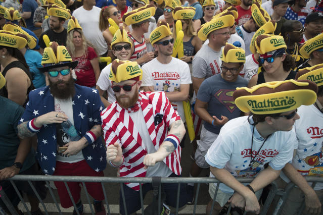 <p>Jeremiah Bruckart, left, and Jared Johnston of the Queens borough of New York dance to the music before the start of the Nathan's Famous Fourth of July hot dog eating contest, Wednesday, July 4, 2018, in New York's Coney Island. (Photo: Mary Altaffer/AP) </p>