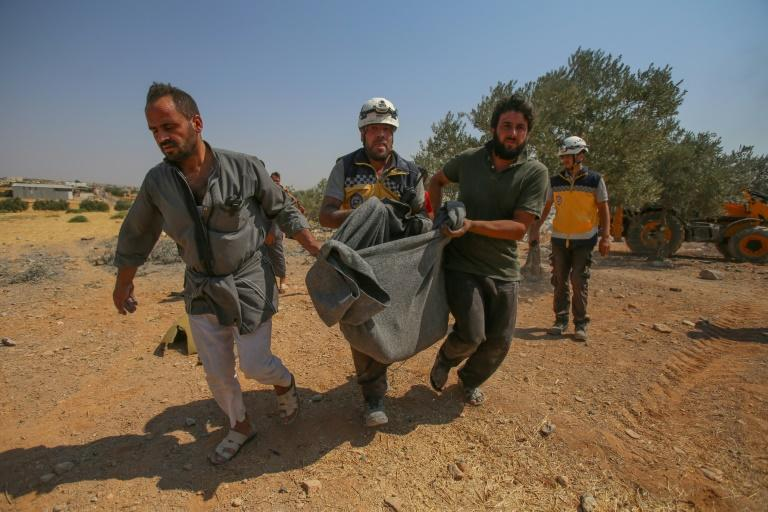 Syrian rescuers carry the victim of reported Syrian regime air strikes that hit a village in the country's northwest, where a mother and six of her children were killed on August 17, 2019 (AFP Photo/Abdulaziz KETAZ)