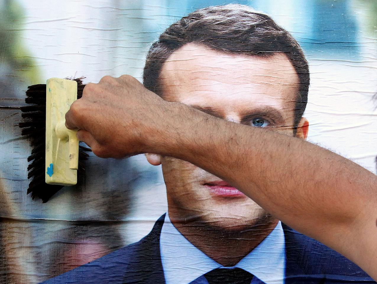 <p>A supporter of French centrist presidential candidate Emmanuel Macron glues a campaign poster to the wall in Bayonne, southwestern France, Wednesday, April 19, 2017. The two-round presidential election is set for April 23 and May 7. (AP Photo/Bob Edme) </p>