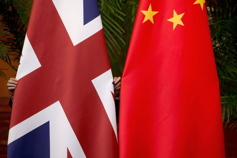 """FILE PHOTO: A worker adjusts British and China national flags on display for a signing ceremony at the seventh UK-China Economic and Financial Dialogue """"Roundtable on Public-Private Partnerships"""" in Beijing"""