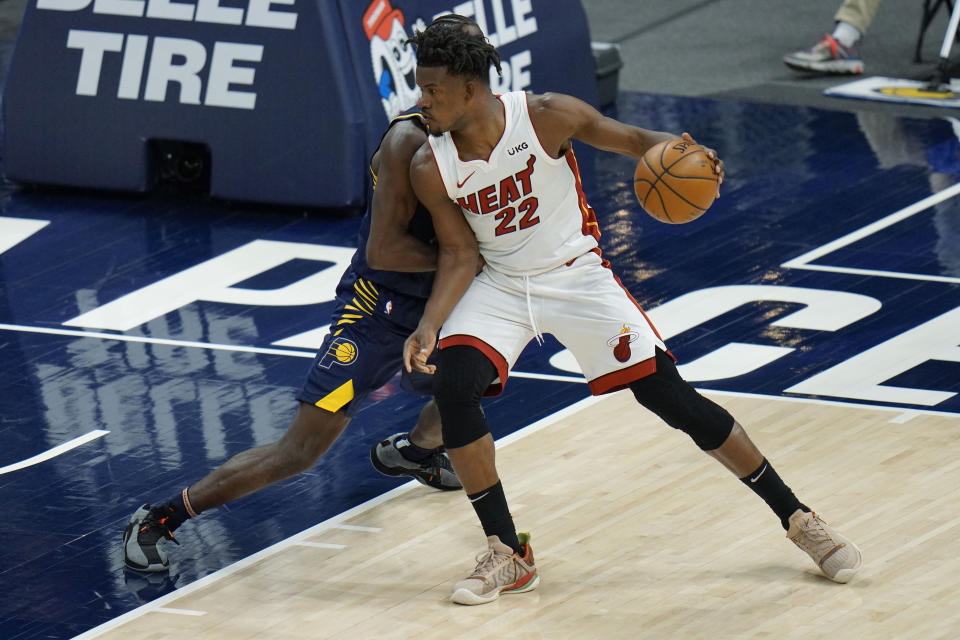 Miami Heat forward Jimmy Butler, right, backs Indiana Pacers guard Caris LeVert to the basket during the first half of an NBA basketball game in Indianapolis, Wednesday, March 31, 2021. (AP Photo/AJ Mast)