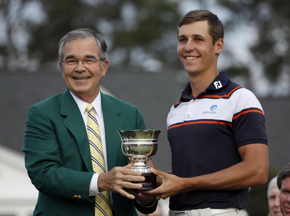 Amateur Oliver Goss, of Australia, is given his trophy by Billy Payne, Chairman of the Augusta National Golf Course, following the Masters golf tournament Sunday, April 13, 2014, in Augusta, Ga. (AP Photo/David J. Phillip)