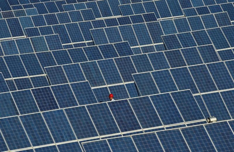 An employee walks between rows of solar panels at a solar power plant on the outskirts of Dunhuang