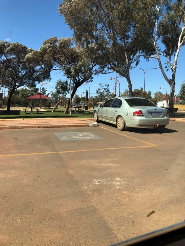 Picture of the car which is parked next to a disabled parking spot, which would prohibit access for someone who needs the disabled parking bay.