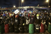 Protesters stand with shields and helmets at an intersection, during an anti-government march in Bogota, Colombia, Wednesday night, May 12, 2021. Colombians have taken to the streets for weeks across the country, after the government proposed tax increases on public services, fuel, wages and pensions, but have continued even after President Ivan Duque walked back the tax hike. (AP Photo/Ivan Valencia)