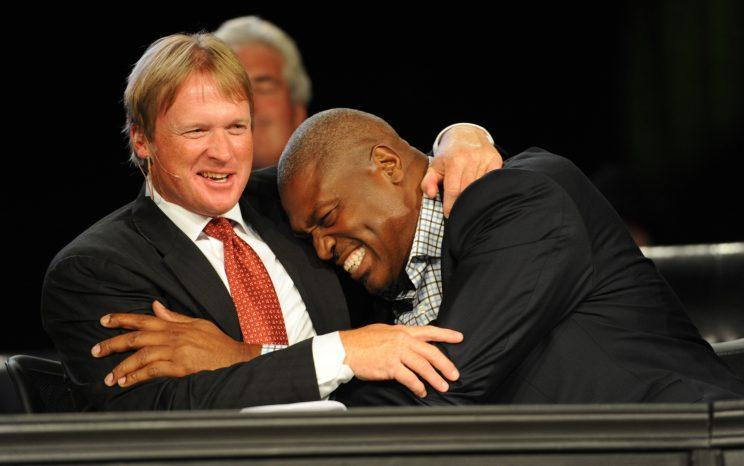 Jon Gruden, getting a hug from Charles Haley, said he wants to coach in the NFL again. (AP)