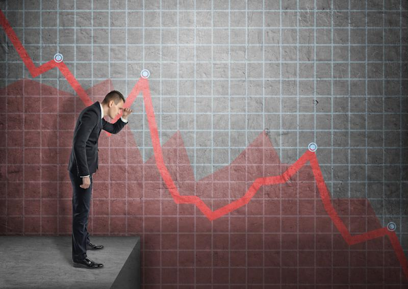 A businessman looking at a line chart plunging downward