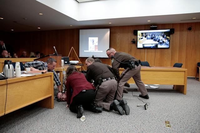 Randall Margraves is tackled after he lunged at Larry Nassar (not seen) a former team USA Gymnastics doctor who pleaded guilty in November 2017 to sexual assault charges, during victim statements of his sentencing in the Eaton County Circuit Court in Charlotte, Michigan, U.S., February 2, 2018. Picture 9 of 10 in series. REUTERS/Rebecca Cook