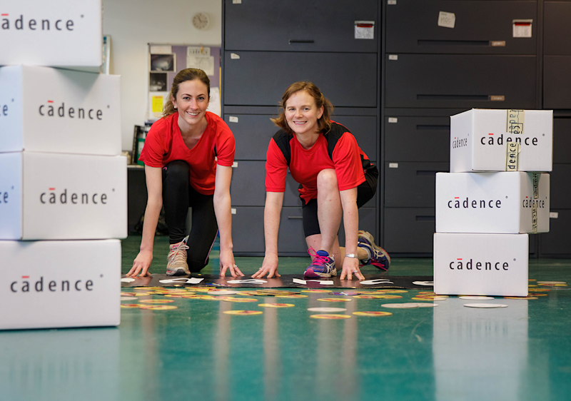 Two women in running outfits, in between two stacks of boxes with the Cadence logo on them