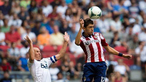 Chivas USA's Marco Delgado, right, gains control of the ball in front of Vancouver Whitecaps' Kenny Miller, of Scotland, during the first half of an MLS soccer game in Vancouver, British Columbia, on Sunday, Sept. 1, 2013. (AP Photo/The Canadian Press, Darryl Dyck)
