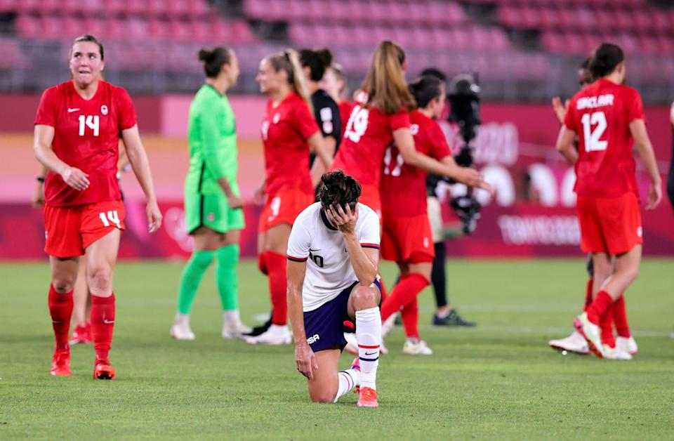 Carli Lloyd kneels in defeat after the USWNT's Olympics loss to Canada.