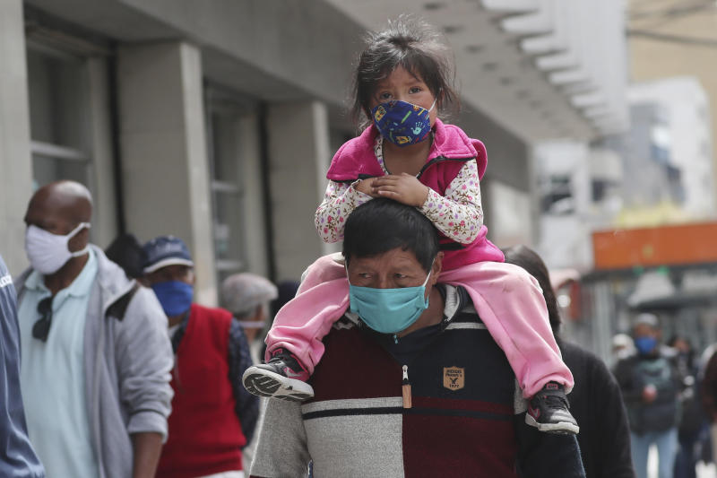 A child, wearing a protective face mask as a mandatory measure to help curb the spread of the new coronavirus, rides piggyback through a crowded downtown area in Quito, Ecuador, Wednesday, June 10, 2020. The city is returning to a new normality after relaxing a rigorous quarantine but amid a certain fear that COVID-19 infections may rise. (AP Photo/Dolores Ochoa)