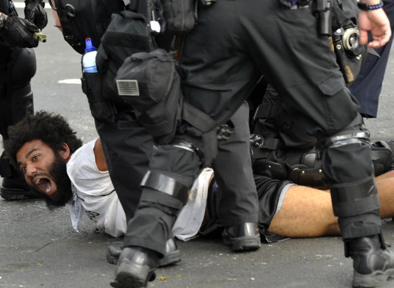 A protester is detained by police at a march and rally during this weekend's NATO summit in Chicago Sunday, May 20, 2012 in Chicago. (AP Photo/Paul Beaty)