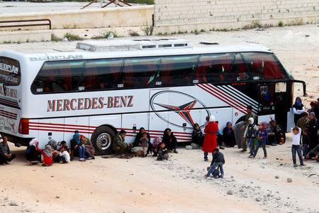 People, who were evacuated from the two rebel-besieged Shi'ite villages of al-Foua and Kefraya, wait near buses at insurgent-held al-Rashideen, to travel to government-controlled Aleppo