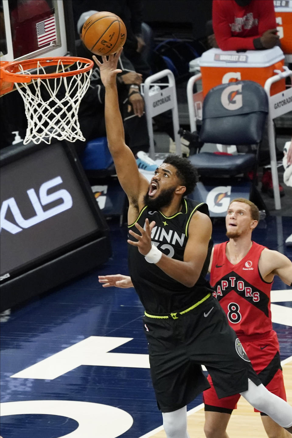 Minnesota Timberwolves' Karl-Anthony Towns (32) lays up a shot as Toronto Raptors' Malachi Flynn (8) watches during the second half of an NBA basketball game Friday, Feb. 19, 2021, in Minneapolis. (AP Photo/Jim Mone)