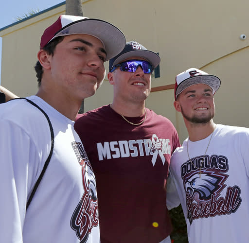Miami Marlins infielder Justin Bour pose for photos with Marjory Stoneman Douglas baseball players Ricky Shimko, left, and Connor Brian before the Marlins' spring training baseball game against the St. Louis Cardinals on Friday, Feb. 23, 2018, in Jupiter, Fla. MLB teams wore hats to honor Marjory Stoneman Douglas High School in Parkland, Fla., where 17 people were fatally shot nine days ago. Stoneman Douglas baseball coach Todd Fitz-Gerald and his two sons were guests of the Houston Astros for their spring opener against the Washington Nationals. Members of the school's baseball and softball teams were guests of the Marlins and mingled on the field with players, coaches and CEO Derek Jeter. (David Santiago/Miami Herald via AP)