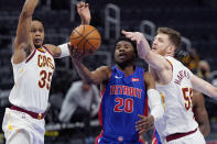 Detroit Pistons guard Josh Jackson (20) attempts a layup as Cleveland Cavaliers forward Isaac Okoro (35) and center Isaiah Hartenstein (55) defend during the second half of an NBA basketball game, Monday, April 19, 2021, in Detroit. (AP Photo/Carlos Osorio)