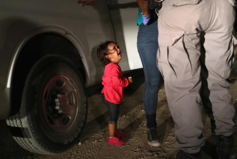 Two-year-old Honduran Yanela Varela cries as her mother is searched and detained in McAllen, Texas, on June 12, 2018, after rafting across the Rio Grande from Mexico