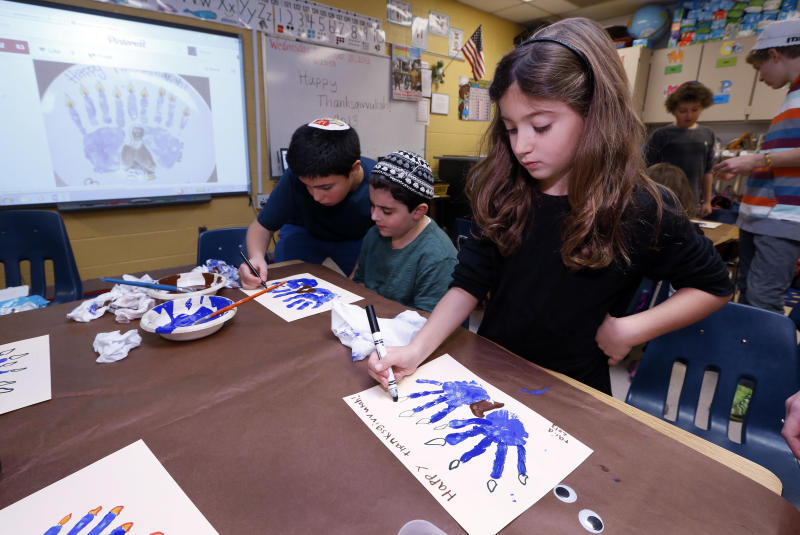 Second-grader Talia Begres, 7, works on creating a menurkey, a paper-and-paint mashup of a menorah and turkey at Hillel Day School in Farmington Hills, Mich., Wednesday, Nov. 20, 2013. The recent class project reflects one way for Jews in the United States to deal with a rare quirk of the calendar that overlaps Thanksgiving with the start of Hanukkah. The last time it happened was 1888 and the next time is 79,043 years from now _ by one estimate that's widely repeated in Jewish circles. (AP Photo/Paul Sancya)