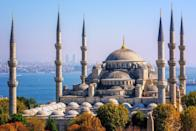 "<p>Nicknamed the Blue Mosque for its expansive walls decked out in Iznik tiles, the <a href=""http://www.bluemosque.co/"" rel=""nofollow noopener"" target=""_blank"" data-ylk=""slk:Sultan Ahmet Mosque"" class=""link rapid-noclick-resp"">Sultan Ahmet Mosque</a> was commissioned by ruler Ahmet I in 1609. The chosen location of the mosque, facing the Hagia Sophia and hippodrome, caused controversy, as it required many established palaces of Ottoman leaders to be demolished. The structure features five main domes, six minarets, eight secondary domes, and 20,000 tiles inside. It's important to remember the mosque still holds religious gatherings to this day, so make sure to respect the prayer schedule and dress code as you plan your visit.<br></p>"