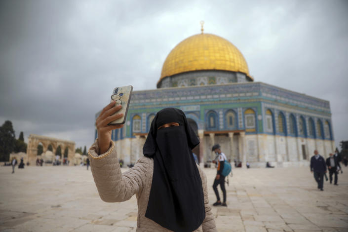 """A Muslim woman takes a photo next to the Dome of the Rock Mosque in the Al Aqsa Mosque compound in Jerusalem's old city, Friday, Nov. 6, 2020. The Palestinian leadership has condemned the United Arab Emirates' decision to forge ties with Israel as a """"betrayal,"""" but it could lead to a tourism bonanza for Palestinians in east Jerusalem as Israel courts wealthy Gulf travelers. (AP Photo/Mahmoud Illean)"""