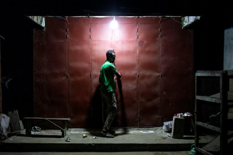 A man closes his shop ahead of Wednesday night's curfew in Dakar