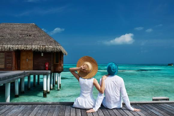 Vacationing couple seated on a beach jetty in the Maldive Islands.